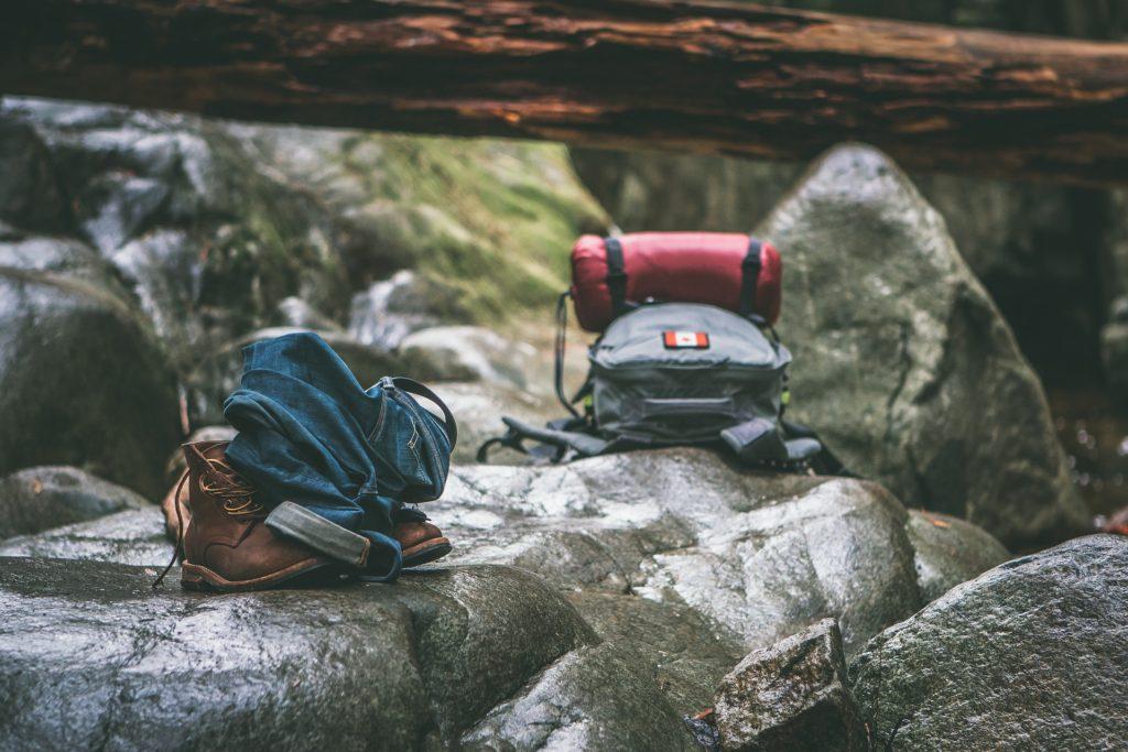 Rucksack auf Steinen im Wald, davor Jeans und ein paar Stiefel